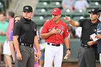 First base umpire Colin Baron, left, with home plate umpire Adam Clark work a game between the Greenville Drive and the Asheville Tourists on Friday, August 23, 2019, at Fluor Field at the West End in Greenville, South Carolina. At center is Drive manager Iggy Suarez. Greenville won, 11-1. (Tom Priddy/Four Seam Images)