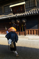 A buddhist monk walks past a sake brewery, Kurashiki, Okayama Prefecture, Japan, July 11, 2013. The historic city of Kurashiki is popular with tourists for its fine Edo Period(1603-1868) and Meiji Period (1868-1912) architecture.