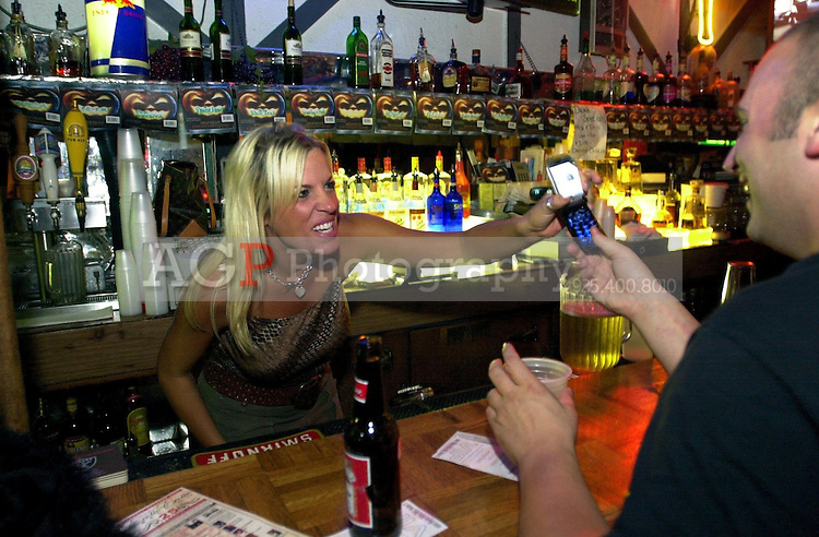 Oct 21, 2004 - Pleasanton, California, USA - 11:39 PM: Union Jack Pub bartender Jenny Dawkins shows customer Mike Skillings a picture of him on her camera phone during Karaoke night at the bar in Pleasanton, Calif., Thursday Oct. 21, 2004. The Union Jack gets going at full steam around midnight..(Credit Image: © Alan Greth)