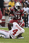 South Carolina Gamecocks running back Marcus Lattimore (21)  tries for extra yards as Alabama Crimson Tide cornerback Mark Barron (4) makes an ankle tackle.South Carolina beats #1 Alabama 38-21 Final.