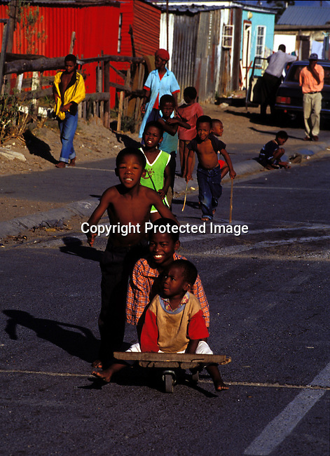 dippchi00280 Children playing on the street on July 21, 2001 in Site B Khayelitsha, a township about 35 kilometers outside Cape Town, South Africa. Khayelitsha is one of the poorest and fastest growing townships in South Africa. Homemade rollerskate board. Street, shacks.©Per-Anders Pettersson/ iAfrika Photos.