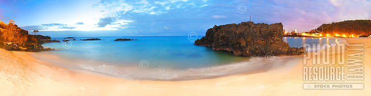 Super wide angle view of Waimea bay at night. Long exposure shot lit by street lights and moon. Jumping rock on the right side. Panoramic high resolution file.
