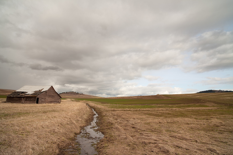 Stormclouds loom above an aging barn along a stream in a remote part of the Palouse farmland in Eastern Washington.