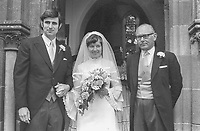 Daughter of N Ireland Chief Justice weds in Kilmore, Co Down - Jonathon Corrall, from Dadby, Leicestershire, with his bride, Shiela Lowry, following their marriage in the local parish church. They are pictured with the bride's father, Sir Robert Lowry. 27th August 1974. 197408270464.<br /> <br /> Copyright Image from Victor Patterson, 54 Dorchester Park, Belfast, UK, BT9 6RJ<br /> <br /> t: +44 28 9066 1296 (from Rep of Ireland 048 9066 1296)<br /> m: +44 7802 353836<br /> <br /> victorpattersonbelfast@gmail.com<br /> www.victorpatterson.com<br /> <br /> Please see my Terms and Conditions of Use at https://www.victorpatterson.com/page2<br /> It is IMPORTANT that you familiarise yourself with them.<br /> <br /> Images used on the Internet incur an additional cost and must be visibly watermarked i.e. © Victor Patterson within the body of the image and copyright metadata must not be deleted. Images used on the Internet have a size restriction of 4kbs and are chargeable at rates available at victorpatterson.com.<br /> <br /> This image is only available for the use of the download recipient i.e. television station, newspaper, magazine, book publisher, etc, and must not be passed on to any third party. It is also downloaded on condition that each and every usage is notified within 7 days to victorpatterson@me.com<br /> <br /> The right of Victor Patterson to be identified as the author is asserted in accordance with The Copyright Designs And Patents Act (1988). All moral rights are asserted.