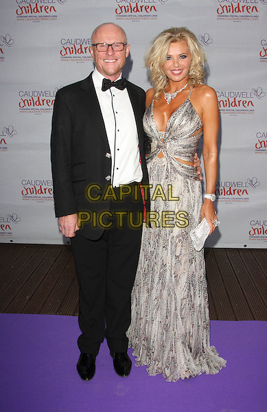 John & Claire Caudwell.Caudwell Childrens' Butterfly Ball at the Battersea Evolution, London, England. September 15th 2011.full length dress tuxedo black grey gray print married husband wife white dress.CAP/JIL.©Jill Mayhew/Capital Pictures