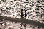 Children playing in the sea at sunset, Store bay, Tobago
