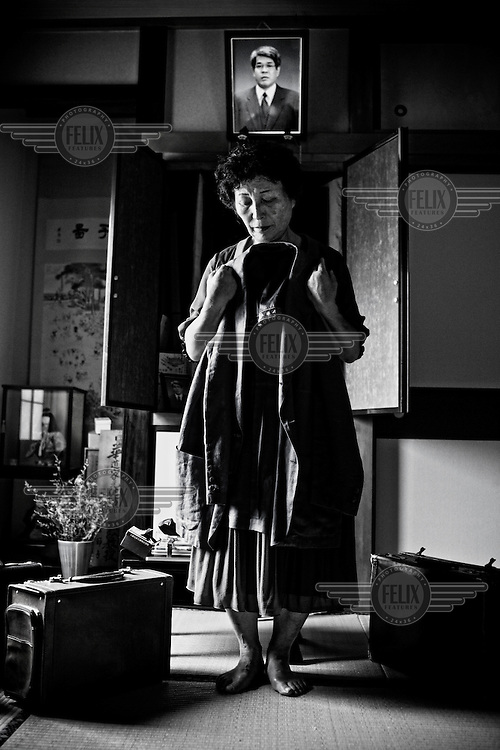 """65 year old Setsuko Nanbu holds her late husband's jacket and briefcase in Ibaraki. Her husband committed suicide in 2004. He jumped onto a train track, leaving a suicide note in his pocket that said, """"I'm sorry. I can't work anymore. I don't know why. I'm really sorry to cause so much trouble for the company.""""  He repeated the apology more than 20 times. Setsuko says, """"Many people apologise in a suicide note. I think it's because they know it's wrong to commit suicide. But they are in such a pain that they feel like death is the only way to escape from the pain and to be relieved."""""""
