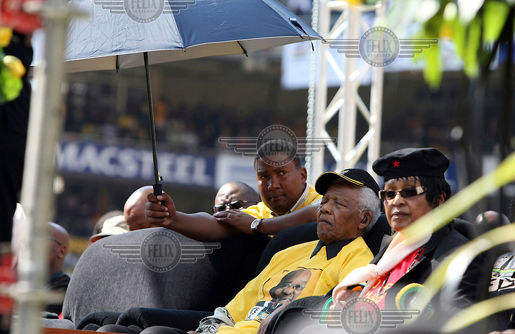 Former president Nelson Mandela at the African National Congress (ANC) party's final Siyanqoba (victory) rally held at the Ellis Park Stadium before the 2009 general election. His grandson Mandla Mandela holds the umbrella and his former wife Winnie Madikizela Mandela sits next to him.