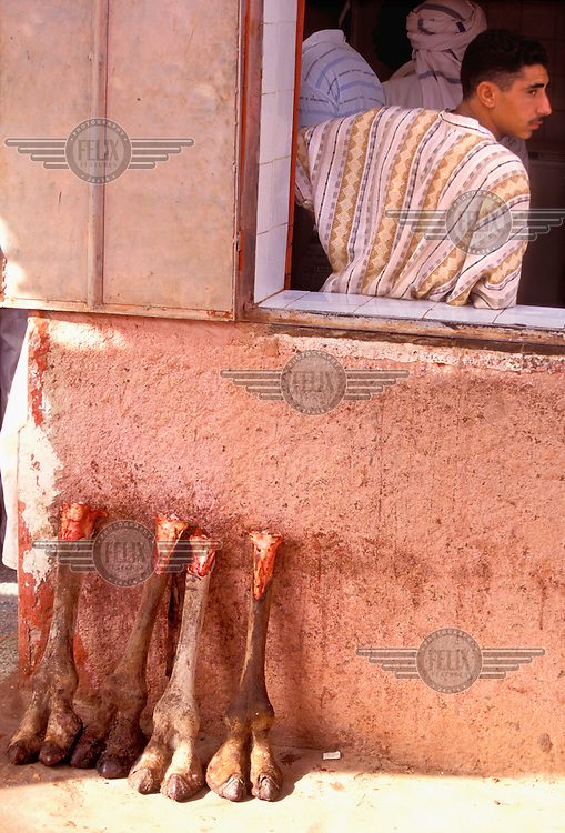 © Andy Johnstone / Panos Pictures..In Salah, ALGERIA. 12/2000...Camel legs for sale outside a butcher's shop.
