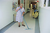 Female domestic assistant from Hotel Services mopping ward corridor,