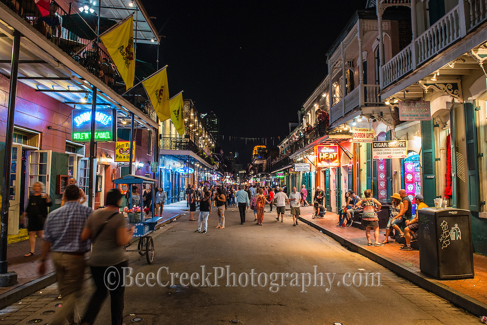 Street scene on Bourbon street on a Staturday night. Let the partying begin.  All the neon signs enticing customers to come in and stay a while.