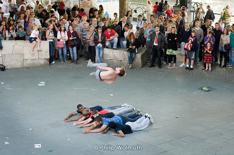 Teenage boys perform acrobatic stunts at the Mayor's Thames Festival 2010, South Bank, London.