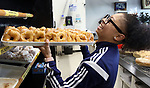 WATERBURY CT. 11 December 2018-121018SV02-Sole Santiago of Waterbury shares a laugh with co workers while puts some donuts on a rack at the Brooklyn Baking Company on Reidville Drive in Waterbury Tuesday.<br /> Steven Valenti Republican-American