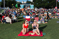 Friends gather at the Blues On The Green free summertime concerts in Zilker Park and enjoy a glass of wine.