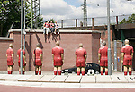 "06 June 2006: A sculpture of three soccer fans sits perched on a wall overlooking another sculpture titled ""Elf Freunde"", or ""Eleven Friends"" is situated in a roundabout near Fritz-Walter Stadium in  Kaiserslautern site of several games during the FIFA 2006 World Cup."