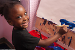 Education preschool portrait of smiling 3 year old girl at easel, painting