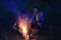 Around the fire, they men protect themselves from stings while waiting for the dark of night. ///Autour du feu, l'on se protège des piqures avant la récolte en attendant la nuit noire.