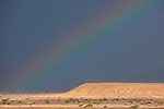 Rainbow on dark rainy sky in the Sahara desert of Morocco.