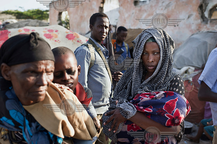 A woman holds her baby at an IDP (internally displaced persons) camp in Mogadishu. The people staying here fled famine in South Somalia. Local militiamen are in the background.