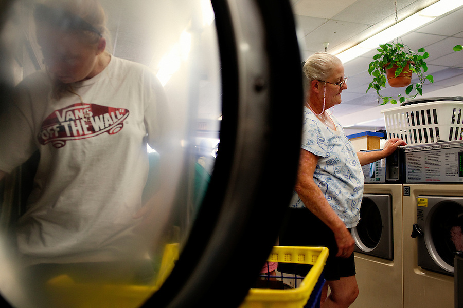 """Ventura, California, August 3, 2010 - Robin Ferguson, right, helps her daughter Haley Eldridge with their laundry at Mission Plaza Laundry. The first Tuesday of each month, Loads of Love pays for low income and homeless to come in to do their laundry. Ms. Ferguson lived in a home with her 2 sons, daughter-in-law and newborn granddaughter up until 2007, when she and one of her sons lost their jobs. They were unable to keep up with the rent and were forced to move to the back patio of her parent's home. """"It was so cold during the winter because it was just a roof over the porch,"""" says Ms. Ferguson. Last year she says a neighbor called the City's code enforcement who gave her seven hours to move everything out. She moved into her van where she has lived since. Ms. Ferguson has a job - she works as a noon aide at Will Rogers Elementary - but she says she does not make enough to rent a home or apartment. Just this month, after three years of waiting, she was finally approved for low income housing assistance. She says that she is so happy that she will be off of the streets. """"I am grateful - just being able to feel like a complete person, self sufficient, not having to depend on some else to have a safe place to be."""" ...."""