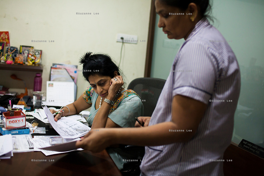 Dr. Nayana Patel, sits at her desk in her Akanksha IVF and surrogacy center that she founded with her husband, Dr. Hitesh, in Anand, Gujarat, India on 10th December 2012. She had done her first successful surrogacy birth in 2003, and has delivered over 565 babies since the clinic's establishment. When choosing surrogates, they are counseled, and screened following a stringent guideline. Surrogates must be married and have completed their own families with their own children, and the couple must be medically, physically, psychologically, emotionally and mentally sound. While 15% of couples are infertile globally, only 6% of infertility cases require surrogacy as a last option. Photo by Suzanne Lee / Marie-Claire France