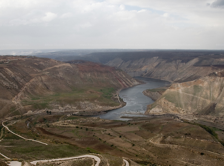 The northern border of Jordan, shared with Syria, is defined for part of its length by the Yarmouk River.  To the left (south) side of the river is Jordan, to the right (north) is Syria.  Straight ahead, the Golan Heights.  The al-Wuheda Dam blocks the Yarmouk River in the foreground.  © Rick Collier