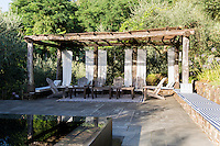 Adirondack chairs in the pergola by the mirror pool in the secluded garden.