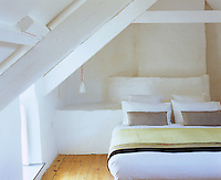 Underneath the exposed A-frame roof of the lime-washed bedroom light streams in from windows located on either side