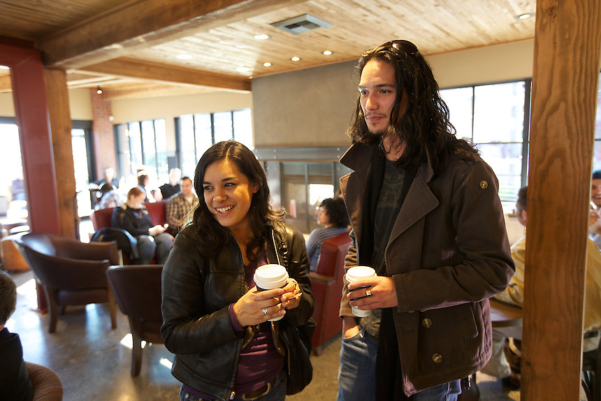 10/17/10 3:33:54 PM -- Seattle, WA, U.S.A - Ashden Trujillo, left, of Seattle and Kawika Sweeney of Seattle enjoy a cup of coffee in the newly remodeled Starbucks in Seattle. Starbucks is now offering wine, beer and dinner fare at their stores.