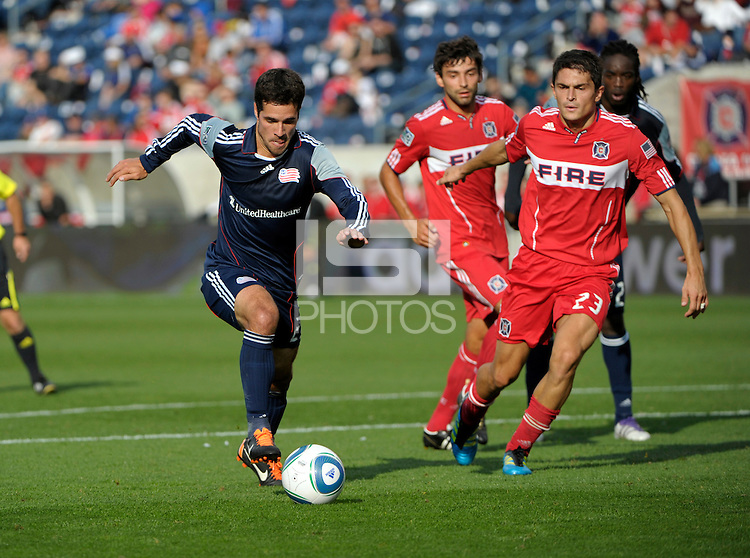 New England midfielder Benny Feilhaber (22) dribbles away from Chicago midfielder Baggio Husidic (9) and defender Josip Mikulic (23).  The Chicago Fire defeated the New England Revolution 3-2 at Toyota Park in Bridgeview, IL on Sept. 25, 2011.