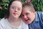 Portrait of teenage boy and girl with Downs Syndrome standing together in park.  MR