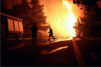 Pictured: Firemen battle with flames in Kalamos.<br /> Re: A forest fire has been raging in the area of Kalamos, 20 miles north-east of Athens in Greece. There have been power cuts, country houses burned and children camps evacuated from the area.