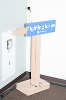 """A podium with a """"Fighting For Us"""" campaign sign stands in a corner after Democratic presidential candidate and former First Lady and Secretary of State Hillary Rodham Clinton spoke at the Women's Economic Opportunity Summit at Southern New Hampshire University in Hooksett, New Hampshire."""