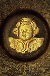 Head and wings of cherub painted gold lying in centre of ornately patterned gold and brown ceramic