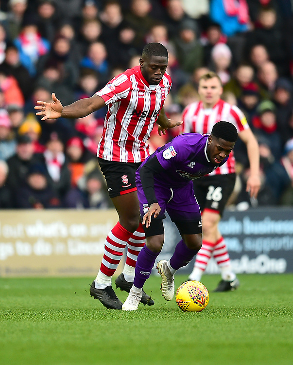Grimsby Town's Mitch Rose shields the ball from Lincoln City's John Akinde<br /> <br /> Photographer Andrew Vaughan/CameraSport<br /> <br /> The EFL Sky Bet League Two - Lincoln City v Grimsby Town - Saturday 19 January 2019 - Sincil Bank - Lincoln<br /> <br /> World Copyright &copy; 2019 CameraSport. All rights reserved. 43 Linden Ave. Countesthorpe. Leicester. England. LE8 5PG - Tel: +44 (0) 116 277 4147 - admin@camerasport.com - www.camerasport.com