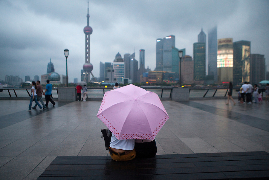 In spite of moderate rain, a couple huddle beneath a pink umbrella and enjoy the view of Shangahi's Bund.
