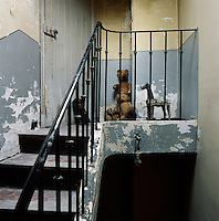 A set of tiled stairs with wrought iron banister and spindles. The walls have a shabby air and neglected teddy bears sit in a corner.