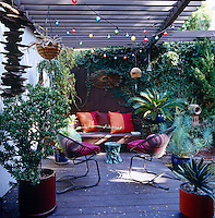 Under a wooden pergola the colourful cushions and plant pots add a touch of fun to this lush outdoor space