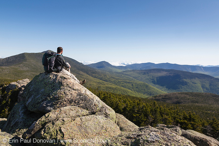 A hiker takes in the view of the Pemigewasset Wilderness from the summit of Mount Liberty in the White Mountains, New Hampshire USA during the summer months.
