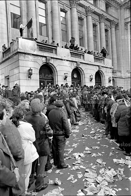 ROMANIA, Pta. Palatului, today Pta. Revolutiei, Bucharest, 22.12.1989<br /> People rise against Ceausescu. After the Ceausescu couple has fled by helicopter around noon, protestors fill the square which originally was guarded by tanks. They aim at the Communist Party Central Committee building. Its balcony is climbed, revolutionary speeches are made.<br /> © Andrei Pandele / EST&OST