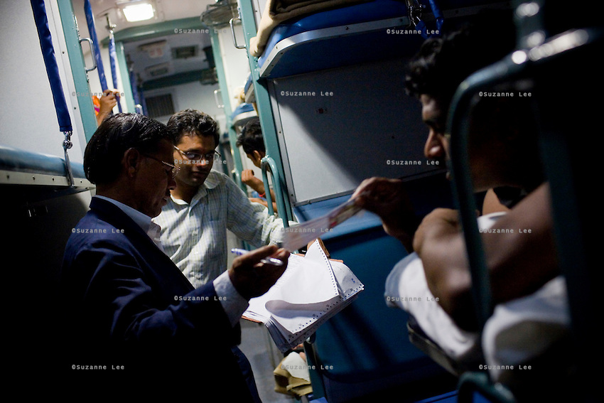 The Train Ticket Examiner (TTE) works his way down the length of the train as train passengers settle in on the Himsagar Express 6318 going from Jammu Tawi station to Kanyakumari on 7th July 2009.. .6318 / Himsagar Express, India's longest single train journey, spanning over 3720 kms, going from the mountains (Hima) to the seas (Sagar), from Jammu and Kashmir state in the Indian Himalayas to Kanyakumari, the southern-most tip of India..Photo by Suzanne Lee / for The National.