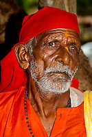 Elderly Indian man with one eye poses for the camera. Anjuna markets - Goa, India.