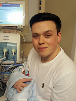 """COPY BY TOM BEDFORD<br /> Pictured: The premature baby held by Luc Protheroe at the Royal Gwent Hospital in Newport, Wales, UK <br /> Re: A young couple were granted their Christmas wish to cwtch their """"miracle"""" baby for the first time.<br /> Little Flynn Protheroe was the same size as a mobile phone when he was born 14 weeks early.<br /> The tiny baby and his mother Paighton Waters, 19, were both given a 50-50 chance of surviving after a rare placental abruption.<br /> Flynn was born by Caesarian and doctors worked on him for 20 minutes to get his tiny heart and lungs working.<br /> Meanwhile Paighton was on the critical list after losing four litres of blood.<br /> But five weeks later the pair are doing well and have been allowed to hold their little boy for a Christmas cuddle.<br /> Proud dad Luc Protheroe, 21, said: """"It's a miracle, I could have lost them both."""