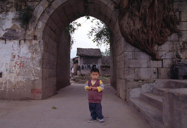 A young boy stands under a stone arch on a rural village street in Dachang, China, Lesser Three Gorges along Daning River