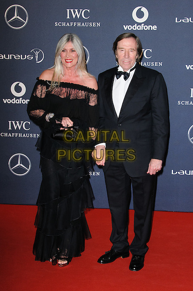 Guenther Netzer & Ehefrau Elvira.Arrivals at the Laureus 2012 World Sports Awards held at the Queen Elizabeth II Centre, London, England..February 6th, 2012.February 6th, 2012.full length black tuxedo dress lace off the shoulder .CAP/CJ.©Chris Joseph/Capital Pictures.