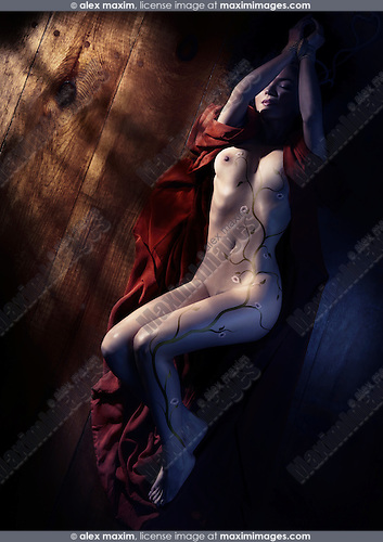 Beautiful naked woman in red kimono with sakura cherry blossom body art and tied hands lying on the floor in dim dramatic light view from above