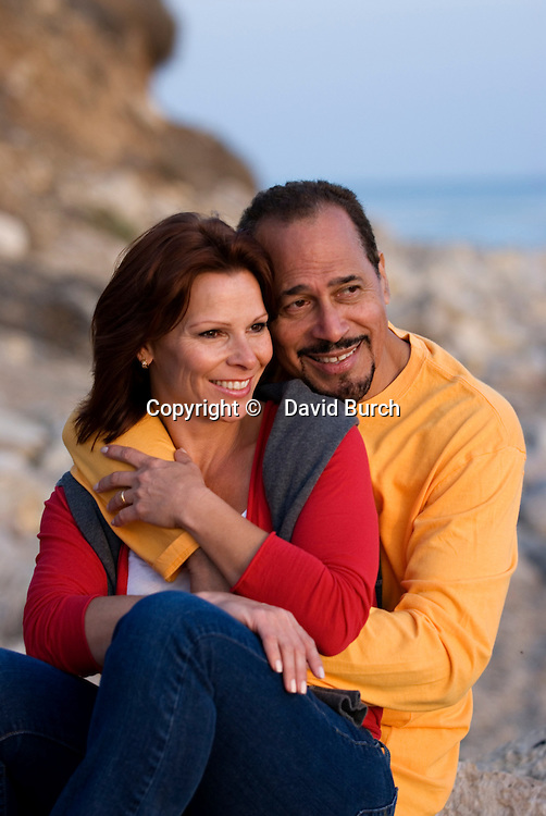 Mature couple smiling at beach, close-up