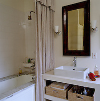 A marble-topped bath and a striped shower curtain that matches the window blind create a simple elegant look