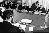 Le Duc Tho, second from upper right, puts his initials to the cease fire agreement, also know as the Paris Peace Accords, as Dr. Henry Kissinger, lower center, and Ambassador William H. Sullivan, Deputy Assistant Secretary of State for East Asian and Pacific Affairs, lower right, and Xuan Thuy, upper right look on.<br /> Credit: White House via CNP