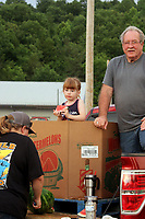 MEGAN DAVIS MCDONALD COUNTY PRESS/Four-year-old Sarah Clay, of Pineville, finds the perfect throne to enjoy her watermelon during Southwest City's 2018 Third of July Celebration. Clay waited patiently while her family helped to distribute a portion of the five tons of free watermelon that was available. More will be available this year as well.